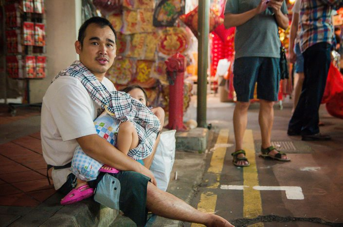 a man with his daughter on the streets of chinatown singapore