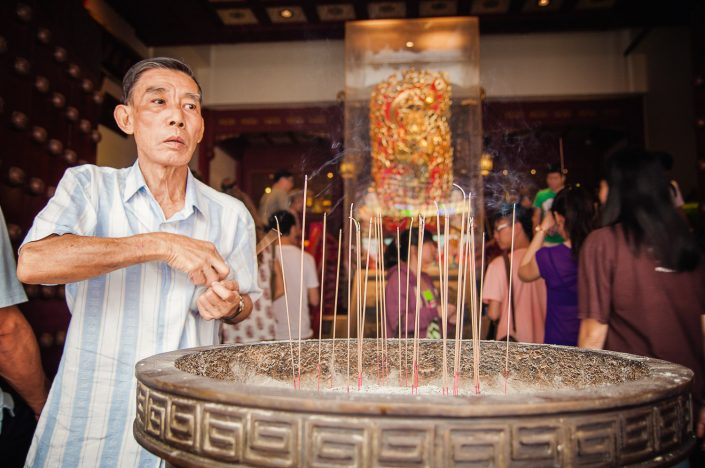 man lighting incense at temple in chinatown singapore