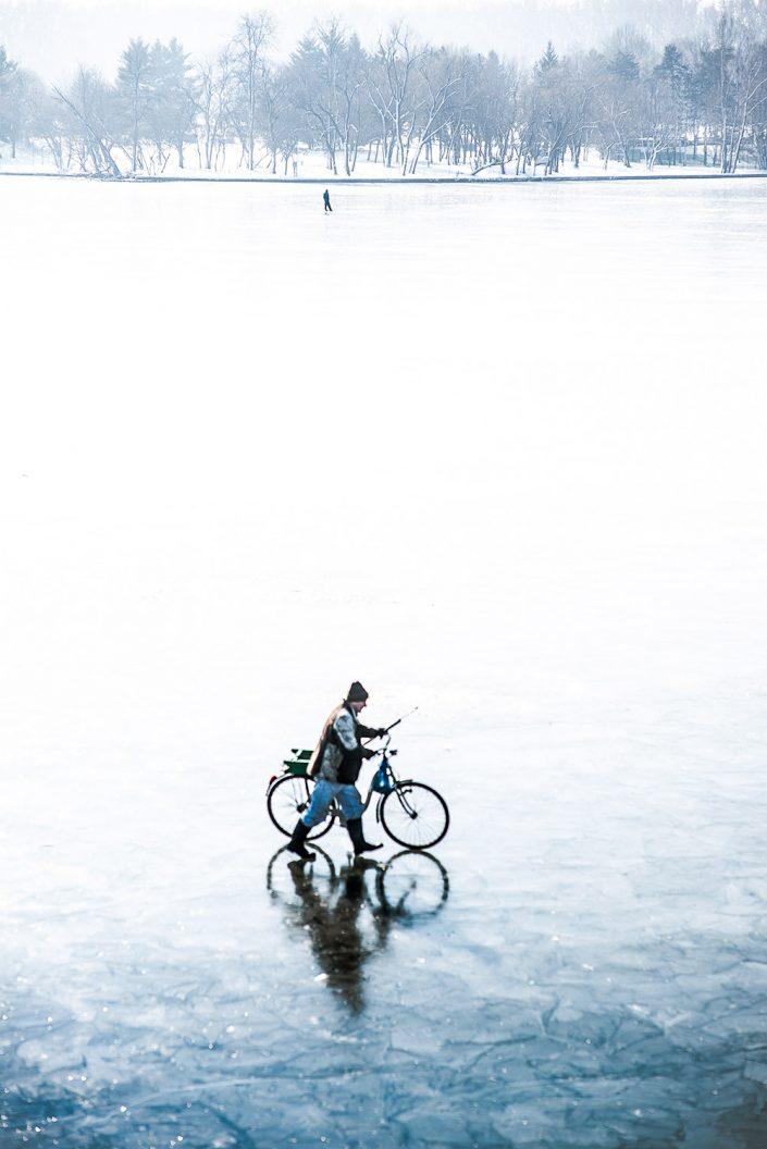 men with bicycle crossing a frozen lake in romania