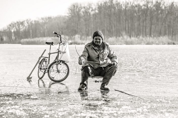 man with bicycle fishing through ice in romania