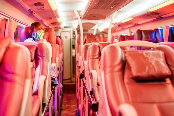 woman with anti smog mask on a sleeper bus in vietnam
