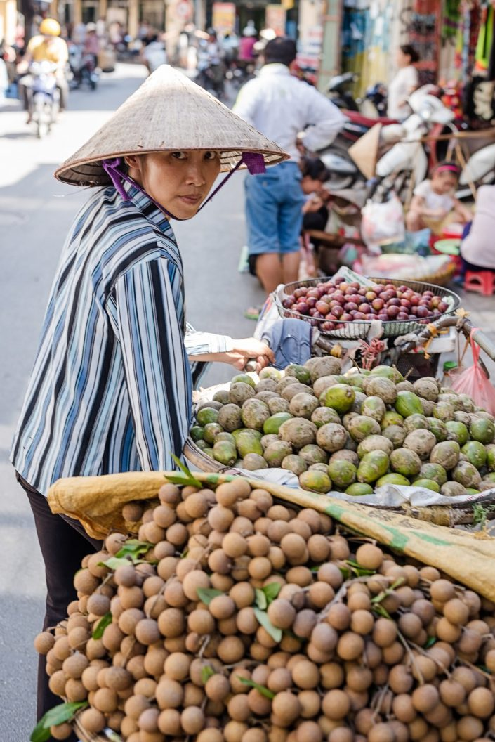 woman with a bicycle selling fruit in hanoi